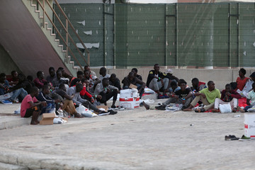 Migrants rest after disembarking a rescue boat at the port of Malaga