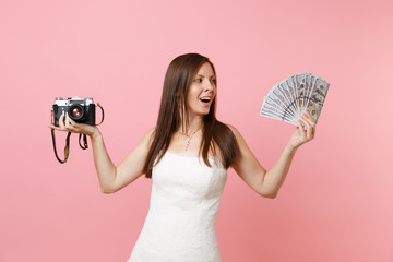 Excited bride woman in wedding dress holding retro vintage photo camera, bundle lots of dollars, cash money choosing staff, photographer isolated on pink background. Organization, Wedding to do list.