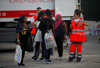 Migrant women are seen led by a member of Spanish Red Cross after disembarking a rescue boat at the port of Malaga