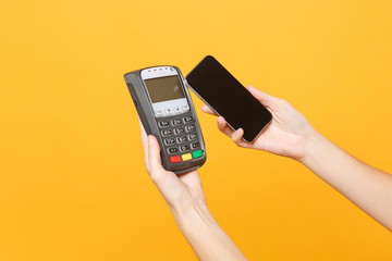 Close up cropped photo female holding in hands wireless modern bank payment terminal to process and acquire credit card payments mobile phone isolated on yellow background. Copy space for advertising.