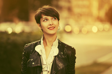 Happy young fashion woman in leather jacket with pixie hair