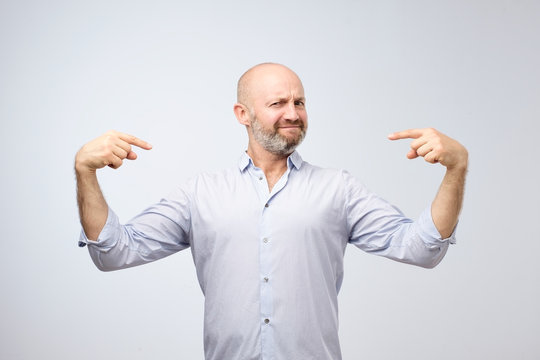 Mature bald adult man with beard standing over grey grunge wall looking confident with smile on face.