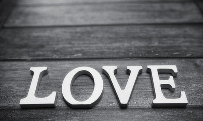 word love made up of white wooden letters on a wooden background