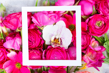 Flowers composition. Floral natural background made of rununculus and orchid fresh flowers with white frame.