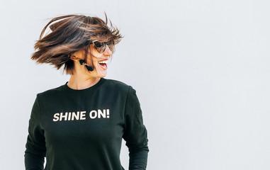 Wall Mural - Happy woman posing in black sweatshirt with fanny print Shine On