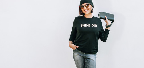 Wall Mural - Woman dressed black outfit with bright accessories stands near wall. Black sweatshirt with Shine On golden print