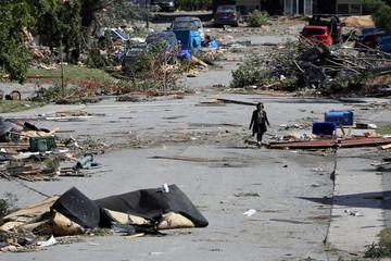 A woman walks past debris after a tornado hit the Mont-Bleu neighbourhood in Gatineau