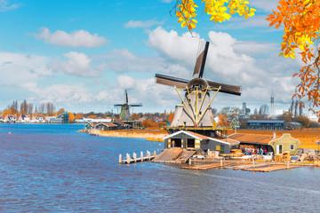 traditional Dutch windmills of Zaanse Schans over water, Netherlands at fall