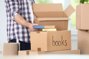 Man putting books into box indoors, closeup. Moving day
