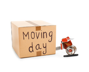 Moving box, marker and adhesive tape dispenser on white background