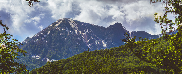 beautiful panorama of the mountains in the early autumn with still green forests