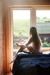 Young woman sitting on bed and enjoying view from window. Peaceful morning