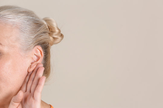 Mature woman with hearing problem on light background, closeup. Space for text