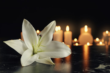 White lily and blurred burning candles on table in darkness, space for text. Funeral symbol Wall mural
