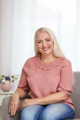 Portrait of beautiful older woman sitting on sofa indoors