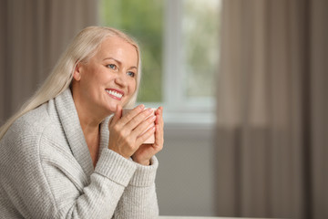 Portrait of beautiful older woman with cup of tea against blurred background. Space for text