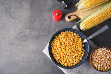 Flat lay composition with corn kernels on grey background. Space for text