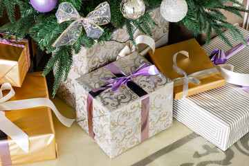 Presents and Gift boxes under Christmas Tree. boxes with ribbon bow. New year decorated house interior. Winter Holiday concept.