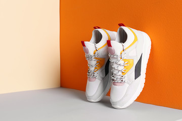 Wall Mural - Pair of stylish sneakers near color wall, space for text
