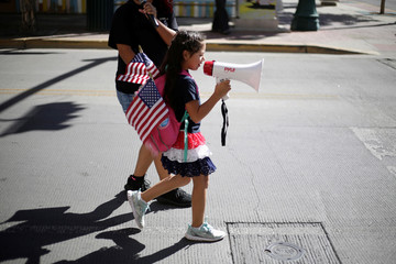 A girl walks as she protests to reject the construction project of a border wall replacement, in downtown El Paso
