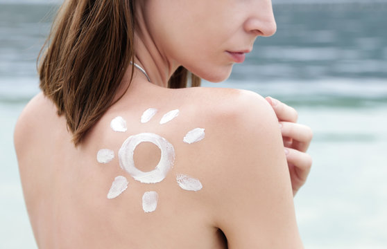 Woman with sun shaped sunscreen on her shoulder, skin protection concept