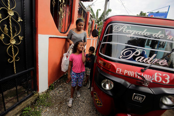 Mariana Ponce, a deportee from the U.S. who was separated from her father Jesus under the Trump administration's hardline immigration policy, smiles as she arrives at her house in La Ceiba