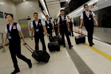 Train attendants walk at the at West Kowloon Terminus at the first day of service of the Hong Kong Section of the Guangzhou-Shenzhen-Hong Kong Express Rail Link, in Hong Kong
