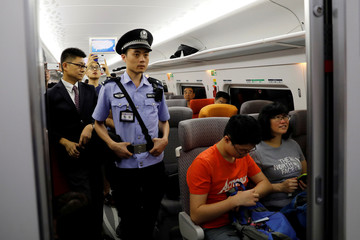 A Chinese policeman patrols a train during the first day of service of the Hong Kong Section of the Guangzhou-Shenzhen-Hong Kong Express Rail Link, in Hong Kong
