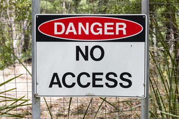 Sign Danger No Access in Australian bushland with wire fence