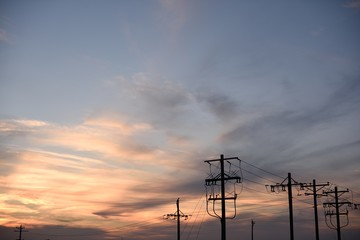 Sunset silhouette of a row of electricity utility poles and high voltage power lines in Wyoming / USA.