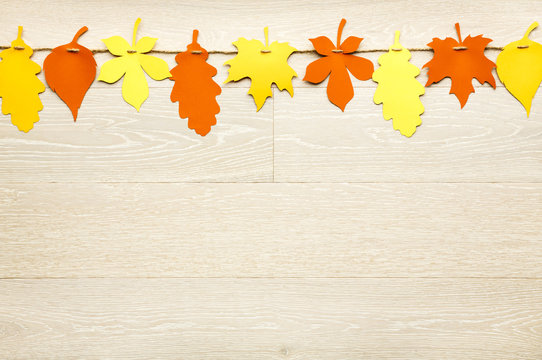 Simple, rustic country style Fall Thanksgiving decorations garland banner of colorful cut paper leaves on whitewashed wood background