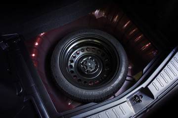 Spare wheel in a car, automotive part concept.