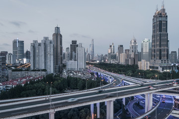 aerial view of buildings and highway interchange at dusk in Shanghai city