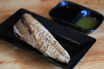 Grilled saba on black dish with dipping soy sauce and green spicy sauce on wooden table