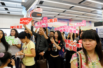 Tour guides greet passengers from China at West Kowloon Terminus at the first day of service of the Hong Kong Section of the Guangzhou-Shenzhen-Hong Kong Express Rail Link, in Hong Kong