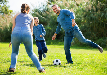 Portrait of active family playing soccer