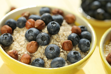 oatmeal porridge with blueberries and hazelnuts. Muesli with berries and nuts.granola and fresh blueberries in a yellow  bowl on a yellow  plank background.Useful breakfast.Healthy Eating