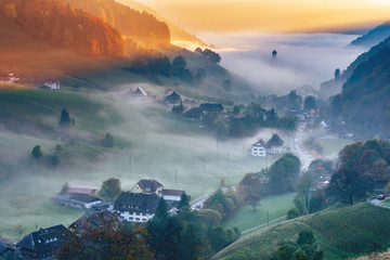 Scenic foggy mountain landscape at sunset. View on a picturesque village in Germany, Black Forest. Colorful travel background.