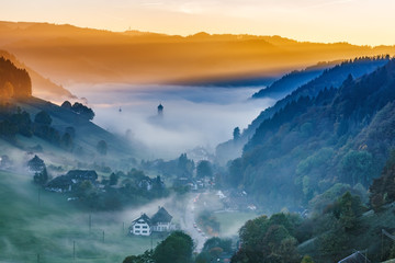 Scenic mountain landscape. View on a picturesque village in Germany, Black Forest, covered in fog. Colorful travel background.