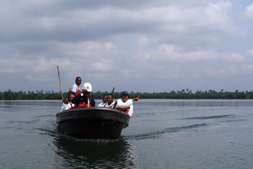 A team of the joint task force, part of the Bodo oil spill clean-up operation, ride a boat in the creeks near the village of Bodo