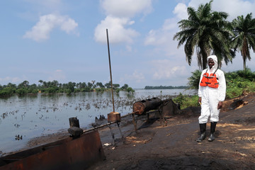 A member of the joint task force, part of the Bodo oil spill clean-up operation, stands near the site of an illegal refinery near the village of Bodo in the Niger Delta
