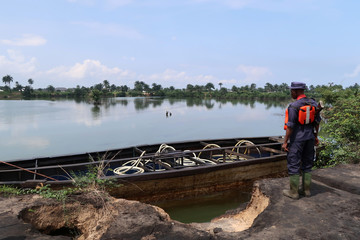 A member of the Nigerian security forces stands next to a barge holding diesel produced from a nearby illegal refinery near the village of Bodo in the Niger Delta