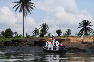 A team of the joint task force, part of the Bodo oil spill clean-up operation, disembarks from a boat at the site of an illegal refinery near the village of Bodo in the Niger Delta