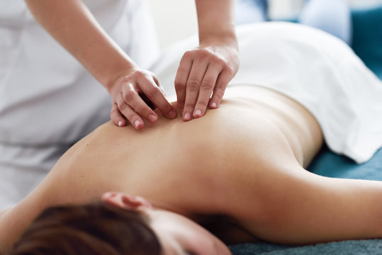 Young woman receiving a back massage by professional therapist.