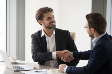 Happy business partners shaking hands after successful negotiations in office, company CEO handshake colleagues thanking for meeting, businessmen handshaking closing deal. Cooperation, interview, hr