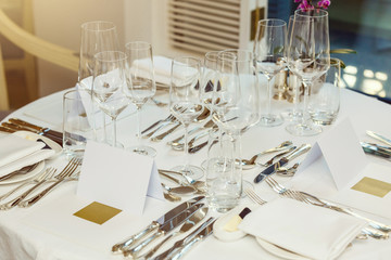 Empty plate, wine glasses, fork and knives on the table. Table setting