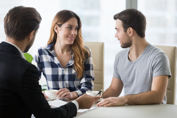 Happy millennial couple visit architect or designer office ready to buy first house together, man and woman look at each other consulting with realtor deciding to move, choosing apartment or flat