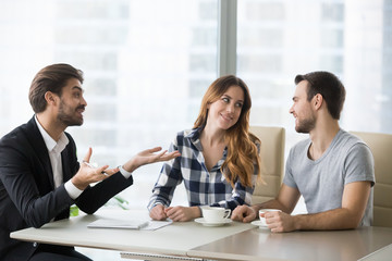 Happy millennial couple look at each other visiting consultant or broker, boyfriend and girlfriend consulting at real estate agent, deciding to make purchase, spouses talk with banker taking loan