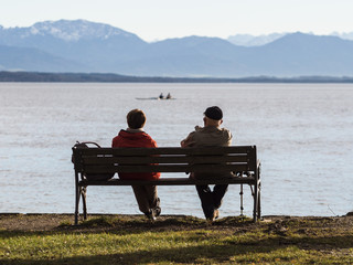 Sitzbank am Ufer des Starnberger Sees mit 2 Rentnern die den Ausblick genießen, Bayern