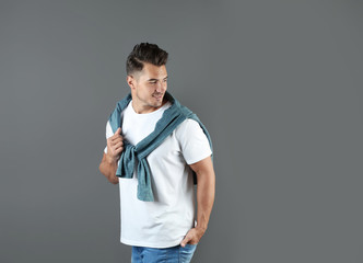 Young man in stylish jeans on grey background